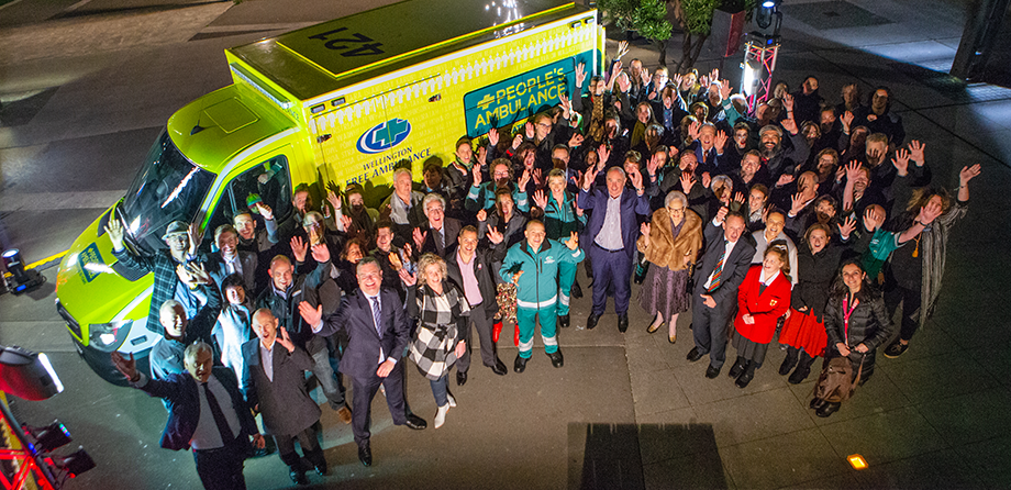 Members of the public alongside staff from Wellington free ambulance, outside an ambulance and waving at camera